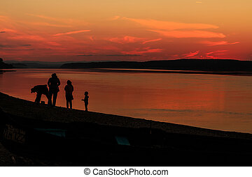 A family with children is walking around the red sunset over...