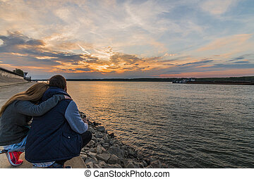 Couple in love watching the sunset over the Danube river