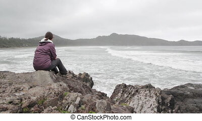 Woman watches the ocean - A woman sits on rocks and...