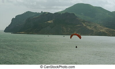 Paraglider fly above the mountains and the sea bay in cloud...