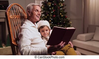 Nice little boy reading a book with his grandfather