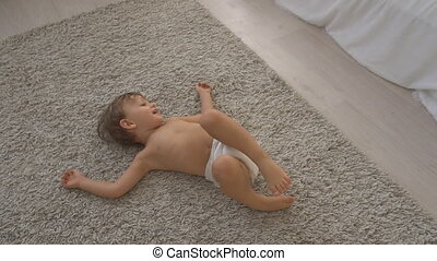 little boy lay on the carpet in the bedroom and plays - the...