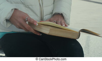 woman flips the pages of the book - close up of woman flips...