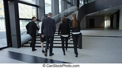 Business people walking in hall - Business people walking in...