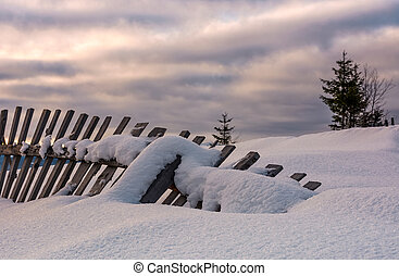 fallen wooden fence on snowy hillside. lovely rural scenery...
