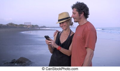 Hand held couple on cell phone at the beach