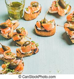 Crostini with smocked salmon, pesto sauce, watercress,...