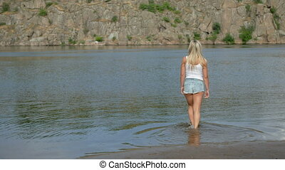 A sexy girl strolls along the shore against