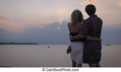 A middle age couple hold one other as they look at the sunset over the ocean
