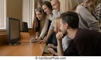 Young people solve problem together in computer room. A...