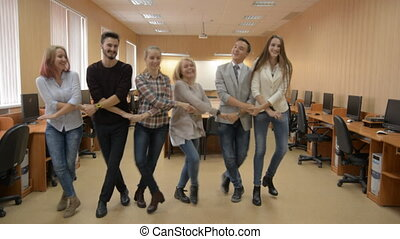 Group of successful people dancing in a computer room. A...