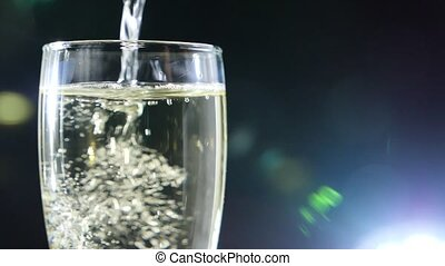 close-up, foaming champagne in a glass on a black...