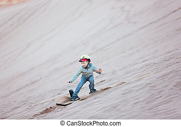 vacation in chile - brave little boy sandboarding in valle...