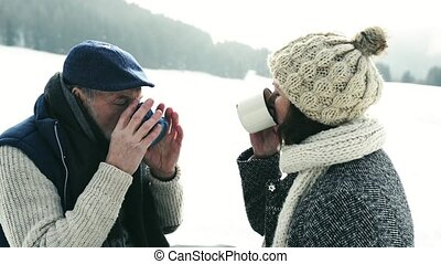 Beautiful senior couple on sledge drinking tea, winter day....