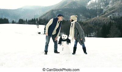 Senior couple enjoying themselves in winter nature. -...