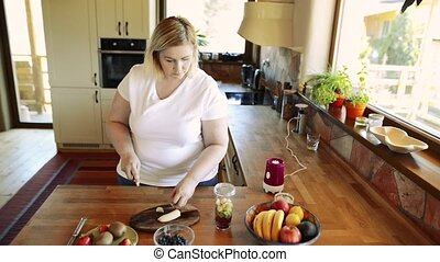 Attractive overweight woman preparing healthy smoothie. -...