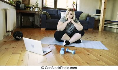 Attractive overweight woman at home working out with...