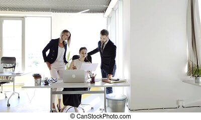 Three business people in the office working together. -...