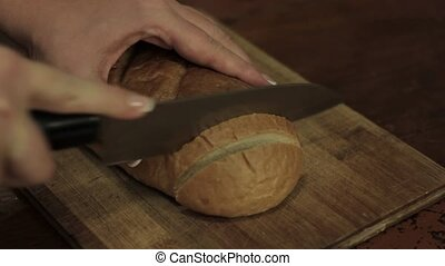 Sliced gray bread. Close-up man hand with knife.