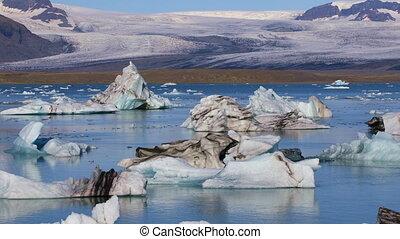 Floating icebergs in glacial lake Jokulsarlon, Iceland -...