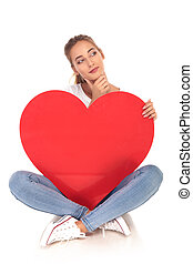 woman holding big red heart is thinking while sitting