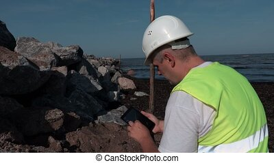 Builder using tablet PC and check the level near pier