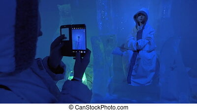 Mother and child visiting ice cave and making photos -...
