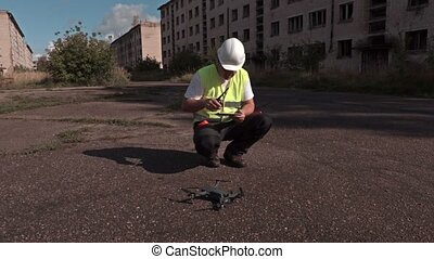 Worker take off drone from the asphalt