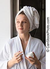 woman applying face cream - pensive young woman in bathrobe...
