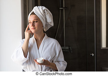 woman applying face cream - attractive young woman with...