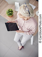 Overhead view of entrepreneur with tablet leaning against...