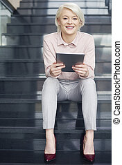 Businesswoman with digital tablet sitting on stairs