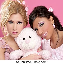 blonde and brunette girls hug a pink teddy bear tender...