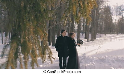happy young lovers in black stand under tall tree Slow...
