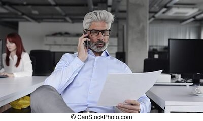 Mature businessman with smartphone in the office. - Mature...
