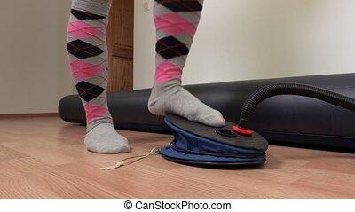 Woman pumping air into the air mattress