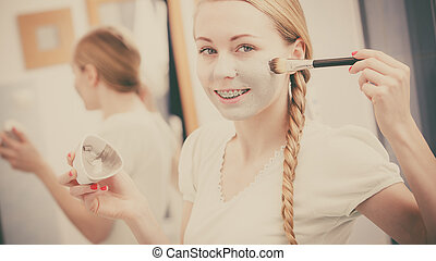Happy young woman applying mud mask on face - Facial dry...