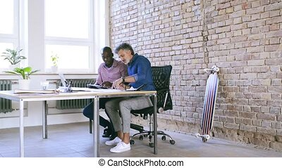 Businessmen in the office working together. - Two...