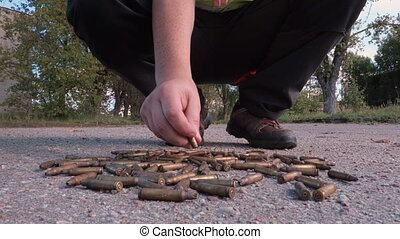 Man collecting bullet shells