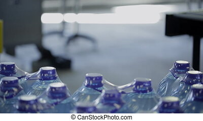 Employee of plant puts packed bottles of water for delivery....