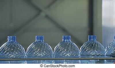 Plastic bottles move along conveyor belt in workshop of...