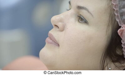 Woman in sterile cap quietly waiting for procedure for...