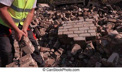 Builder sorting bricks