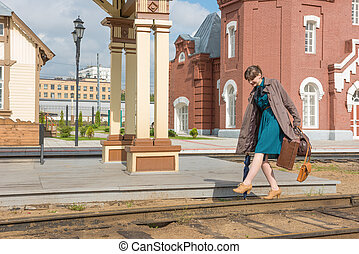 Going on rails. - Young woman walks on rails at a train...
