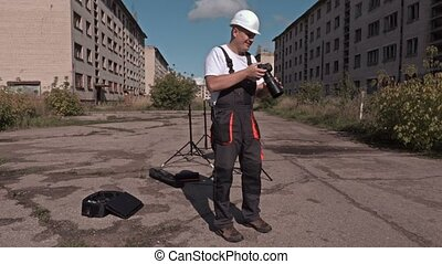 Builder with photo camera at abandoned town