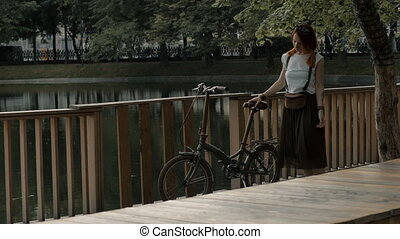 Young woman cyclist standing on a bridge city lake in summer park