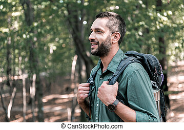 Cheerful male tourist hiking in the woods - Profile of...