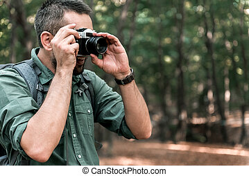 Cheerful male tourist taking photos in forest - Happy man is...