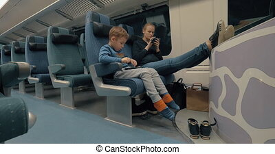 Mother and kid using electronics during train ride - Mother...