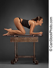 Doggy style. - Young athletic woman in a knee-elbow position...